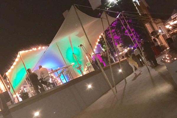 Bury stretch tent hire atatched to wall over high patio extra tall edge poles to accomodate the different levels stretch marquee hire greater manchester uplighters cocktail possuers