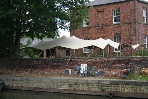 Stretch tent hire over wall around a tree in a confined space. CAT scan to avoid underground service stretch tent rental alternative to wedding marquee hire